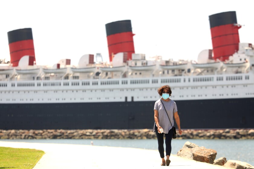 The Queen Mary, seen behind a woman walking on a bike and pedestrian path, has been docked in Long Beach since 1967.