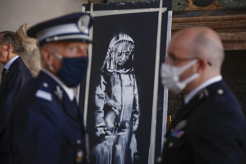 A recovered stolen artwork by British artist Banksy, depicting a young female figure with a mournful expression, that was painted as a tribute to the victims of the 2015 terror attacks at the Bataclan music hall in Paris, is shown during a ceremony at the French Embassy in Rome, Tuesday, July 14, 2020. The work was recovered last June 10 during a search of a home in Tortoreto, a city near the Adriatic coast in the Abruzzo region's Teramo province. (AP Photo/Domenico Stinellis)
