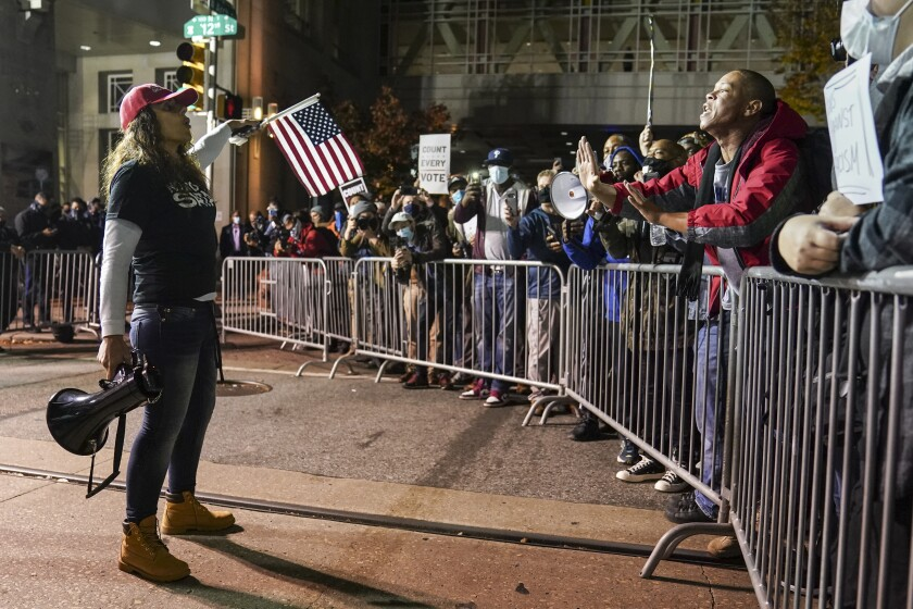 A person with a megaphone talks to people behind a metal barrier
