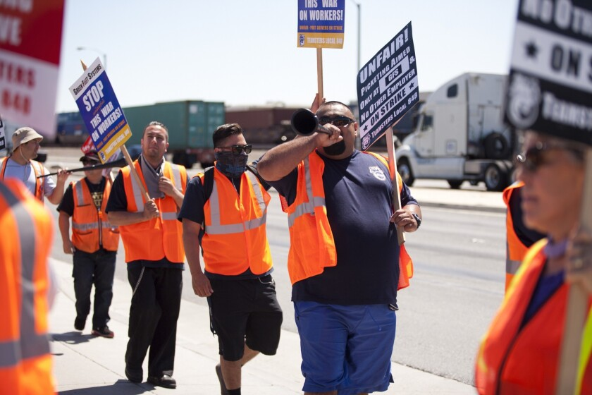 Picketers walk in front of the Green Fleet Systems building in Long Beach on Monday.