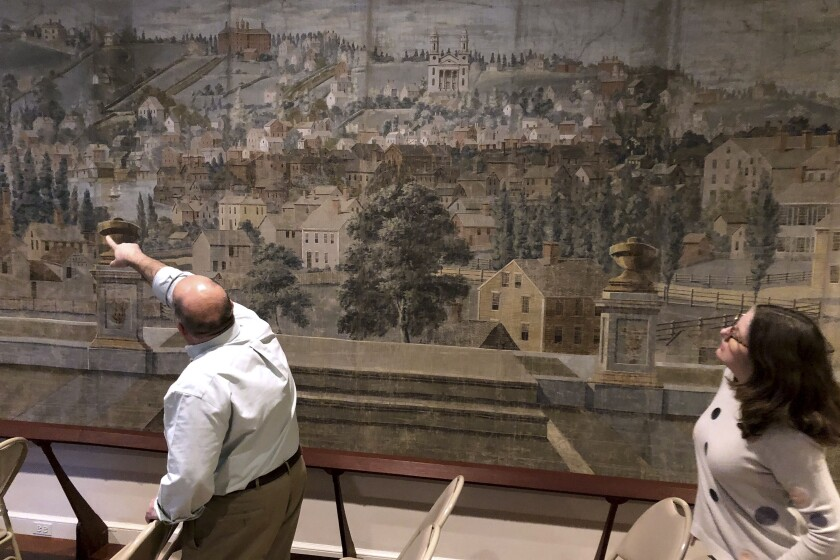 In this Tuesday, Nov. 12, 2019 photo, Rhode Island Historical Society administrators Richard Ring, left, and Morgan Grefe view a restored 210-year-old theater curtain depicting a sweeping view of the city in Providence, R.I. The recently restored drop scene was used in the theater in the early 1800s to entertain audiences between shows. (AP Photo/Jennifer McDermott)