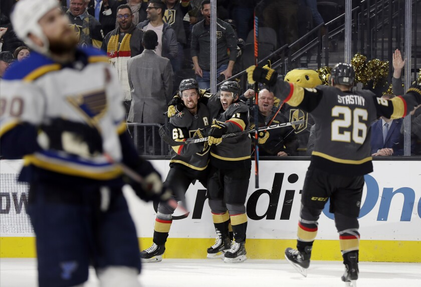 Vegas Golden Knights center Jonathan Marchessault, back right, celebrates with right wing Mark Stone (61) after scoring a power-play goal against the St. Louis Blues in overtime of an NHL hockey game Thursday, Feb. 13, 2020, in Las Vegas. The Golden Knights won 6-5. (AP Photo/Isaac Brekken)