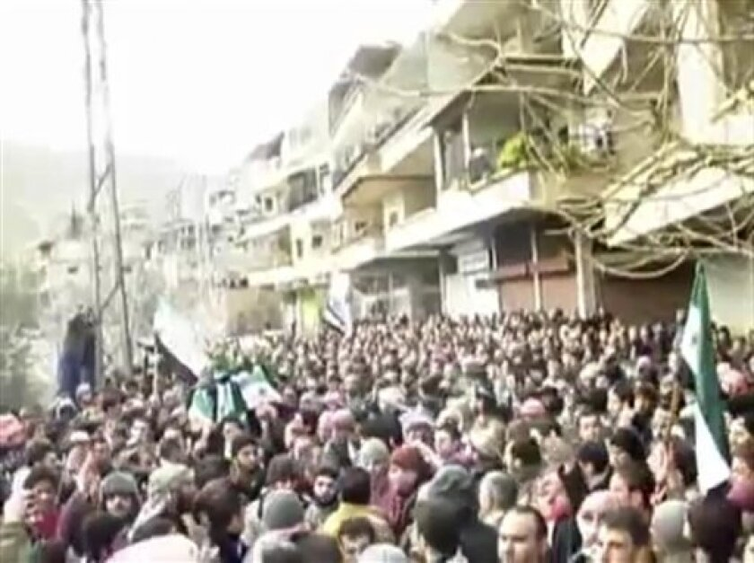 This image from amateur video made available by the Ugarit News group and shot on Sunday, Jan. 29, 2012, purports to show a funeral in Damascus, Syria. The Syrian military launched an offensive to regain control of suburbs on the eastern edge of Damascus on Sunday, storming neighborhoods and clashi