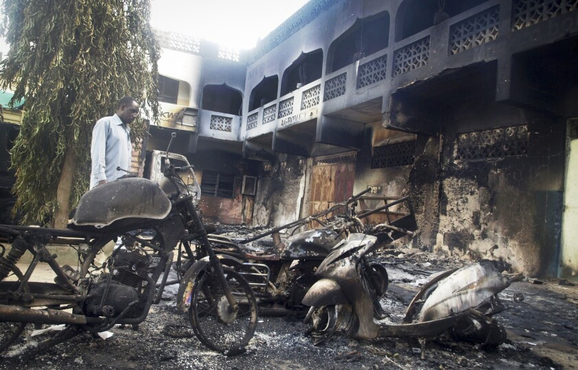 A man observes damage from a brazen attack by gunmen in the Kenyan coastal town of Mpeketoni. Attackers killed dozens of people in siege that began Sunday night.