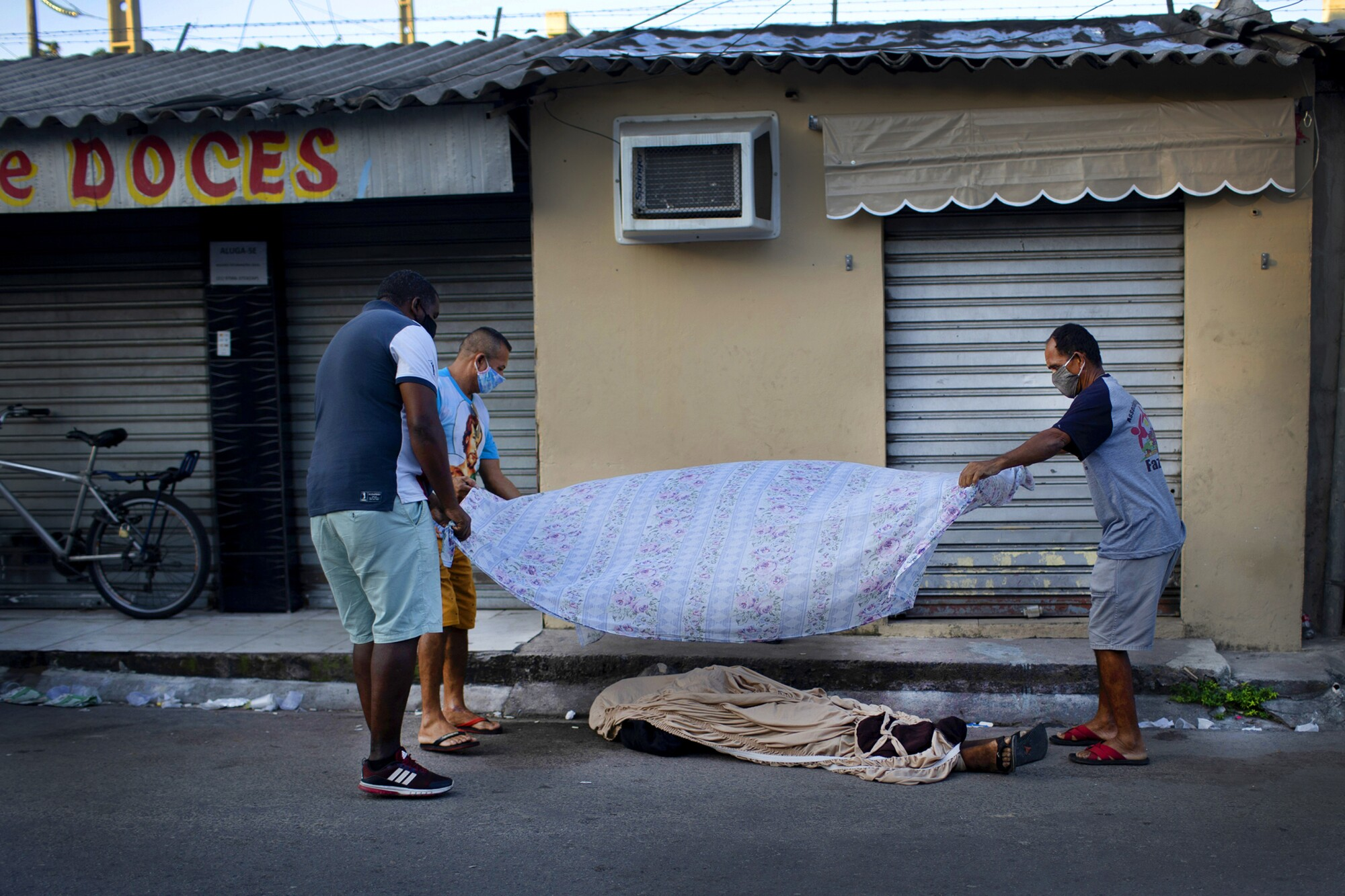 Neighbors cover the the body of 36-year-old Luiz Carlos Da Rocha, who died April 28 in Rio de Janeiro.