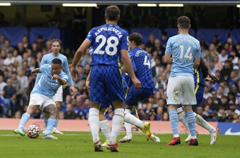 Manchester City's Gabriel Jesus, left, scores his side's opening goal during the English Premier League soccer match between Chelsea and Manchester City at Stamford Bridge Stadium in London, Saturday, Sept. 25, 2021. (AP Photo/Alastair Grant)