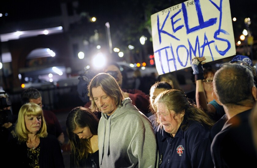"""Friends, family and supporters stand at """"Kelly's Corner"""" on Monday night after two former Fullerton police officers were found not guilty of the murder of Kelly Thomas."""