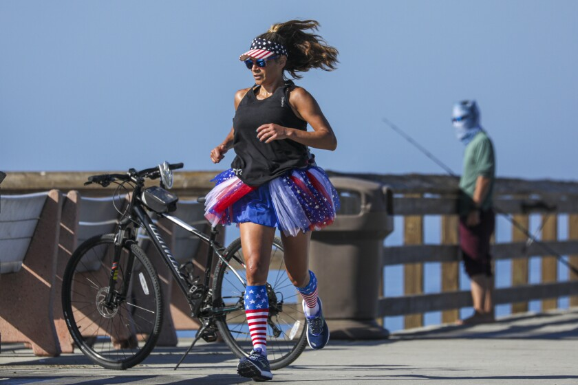On the morning of July 4, Tita Jaramillo runs on Balboa Pier dressed in red, white and blue.