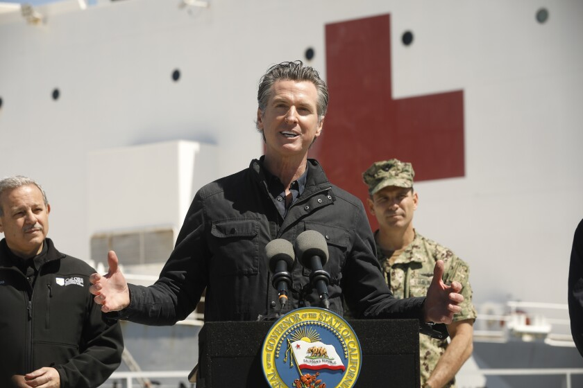 Gov. Gavin Newsom speaks in front of the hospital ship USNS Mercy that arrived into the Port of Los Angeles on Friday.