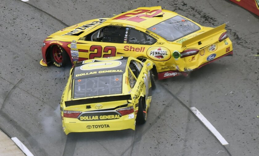 Joey Logano (22) and Matt Kenseth (20) tangle in Ttun 1 during the NASCAR Sprint Cup Series auto race auto race at Martinsville Speedway in Martinsville, Va., Sunday, Nov. 1, 2015. (AP Photo/Don Petersen)