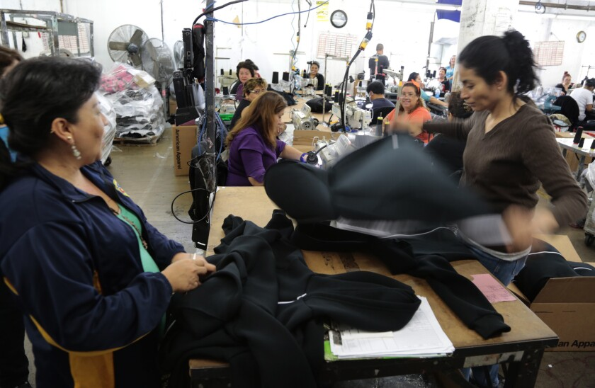 American Apparel is laying off workers as it revamps its production process. Above, employees are seen at the company's downtown Los Angeles headquarters and manfacturing center.