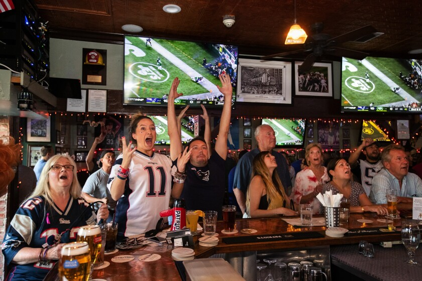 Sports fans and bargoers react to a touchdown by the New England Patriots against the New York Jets.