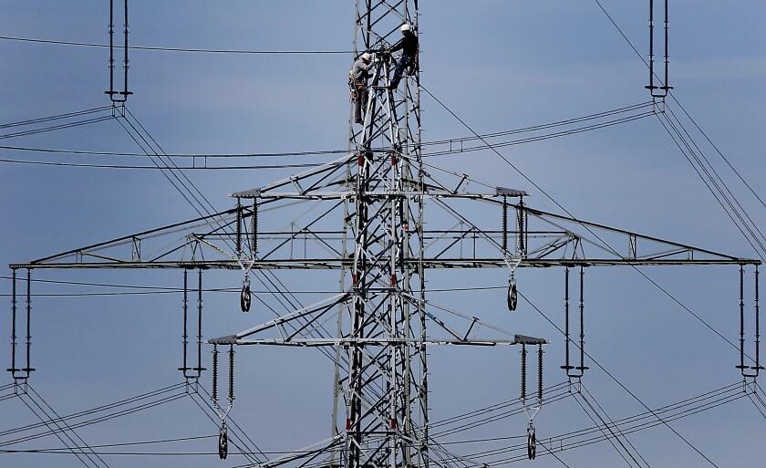 ARCHIVO - En esta foto de archivo del 11 de abril de 2011, empleados de la empresa energética alemana RWE trabajan en una torre de alta energía en Moers, Alemania. Casi 3 millones de trabajadores europeos no pueden pagar la calefacción de sus casas debido a los aumentos de las tarifas de energía, según un estudio realizado por una organización laboral publicado el miércoles 22 de septiembre de 2021. (AP Foto/Frank Augstein, File)