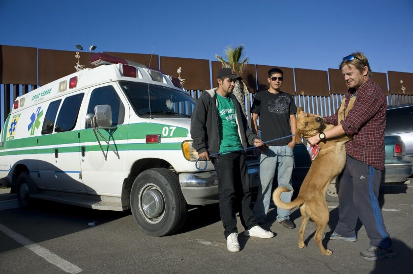 Tom Fremantle and dog  Pancho, at the border fence in Playas de Tijuana on Thursday.  With them are are two volunteers who accompanied them on the last leg of their journey, Erick Alcaraz Robles, 20, left and Javier Felix Ocejo, 18.