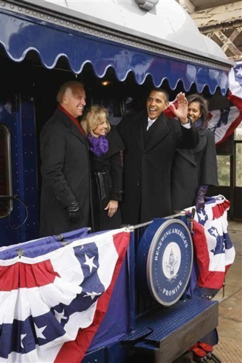 President-elect Barack Obama, accompanied by his wife Michelle, right, and Vice President-elect Joe Biden, and his wife Jill Biden, waves from their train car after a stop on their inaugural whistle stop train trip in Wilmington, Del., Saturday, Jan. 17, 2009. (AP Photo/Charles Dharapak)