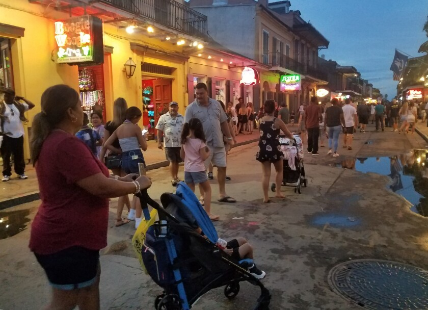 A family walks down Bourbon Street in New Orleans at dusk.