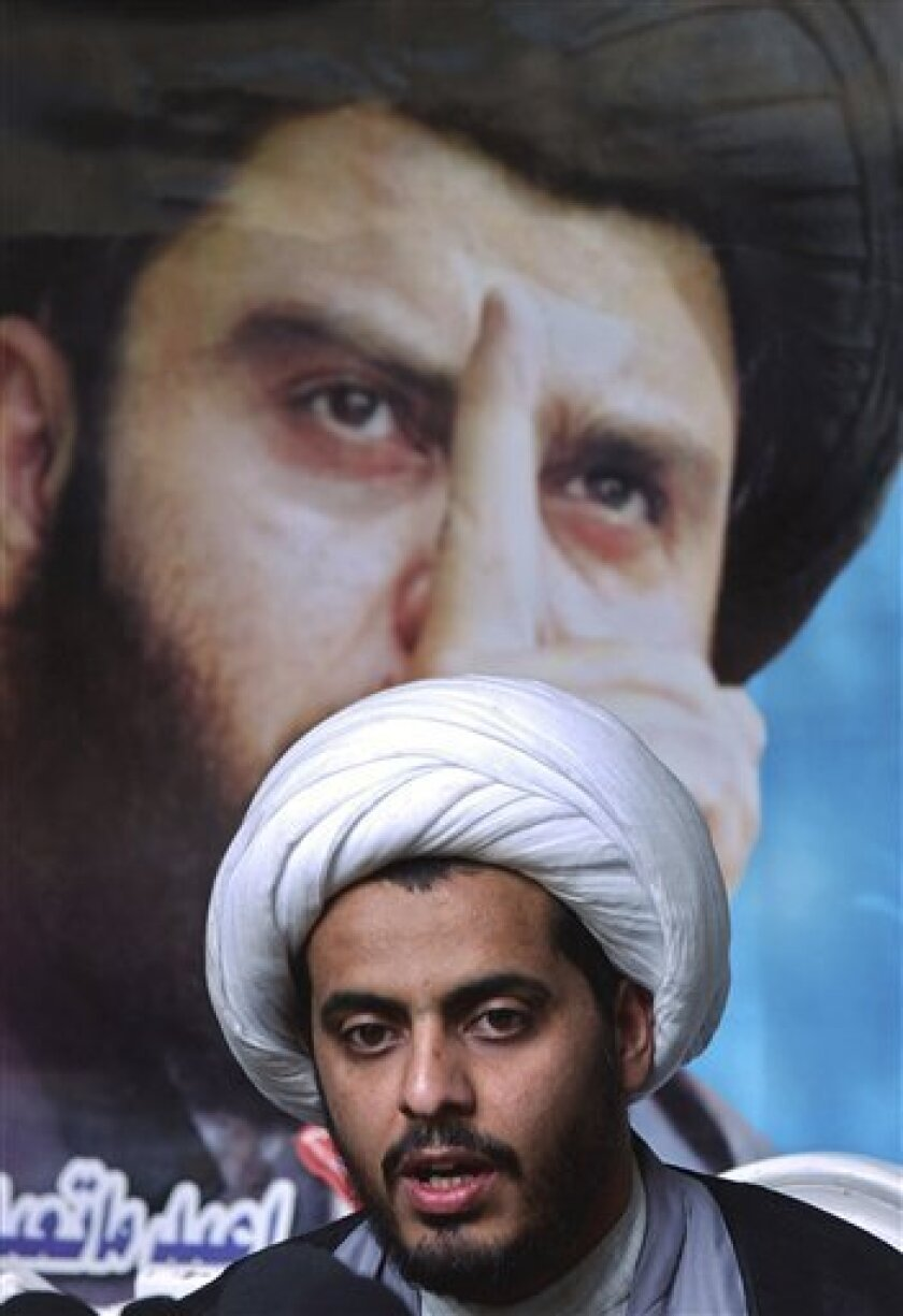 FILE - In this April. 6, 2004, file photo, Qais al-Khazali, then the top aide of radical Shiite cleric Muqtada, al-Sadr, seen in the poster above, speaks during a press conference in Najaf, Iraq. An Iraqi spokesman says authorities have released the leader of a militant group linked to the 2007 kid