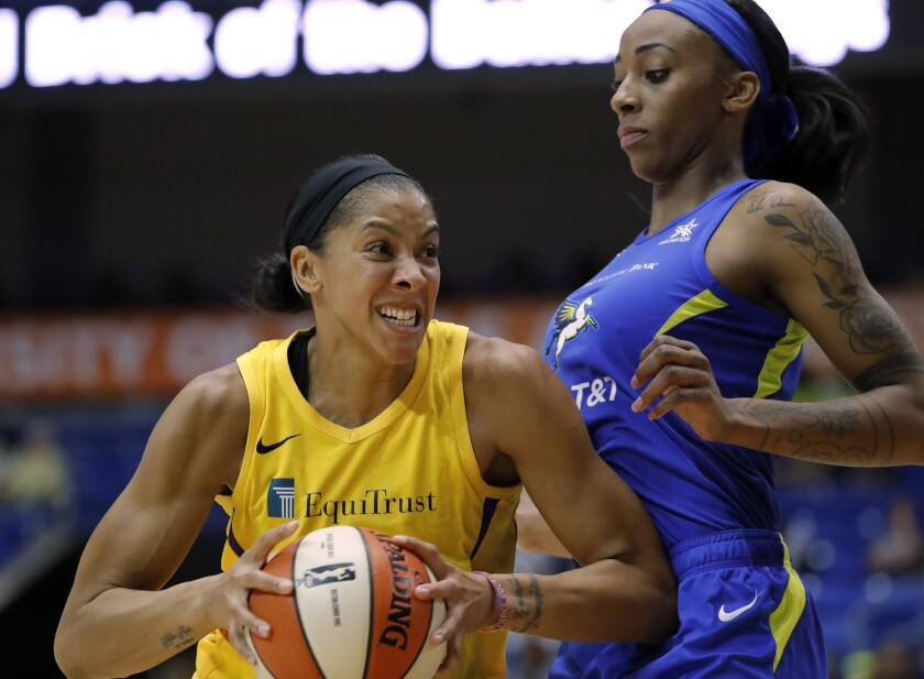 Sparks forward Candace Parker, left, drives to the basket against Dallas Wings' Glory Johnson, right, in the first half on Wednesday in Arlington, Texas.