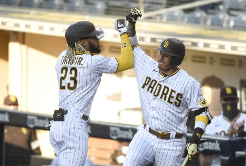 Fernando Tatis Jr. and Manny Machado celebrate after a home run by Tatis on Aug. 7.
