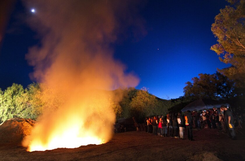 Near the fire, a line of men, boys, and female birdsong dancers from different reservations of the Kumeyaay people sang about safe travels to a better world, and the ocean, mountains and desert during the burning ceremony for Ida Brown, the eldest elder of the Viejas Band of Kumeyaay Indians, who passed away June 11 at the age of 90. During the ceremony, her personal possessions were burned, sending them on their way to the next life.