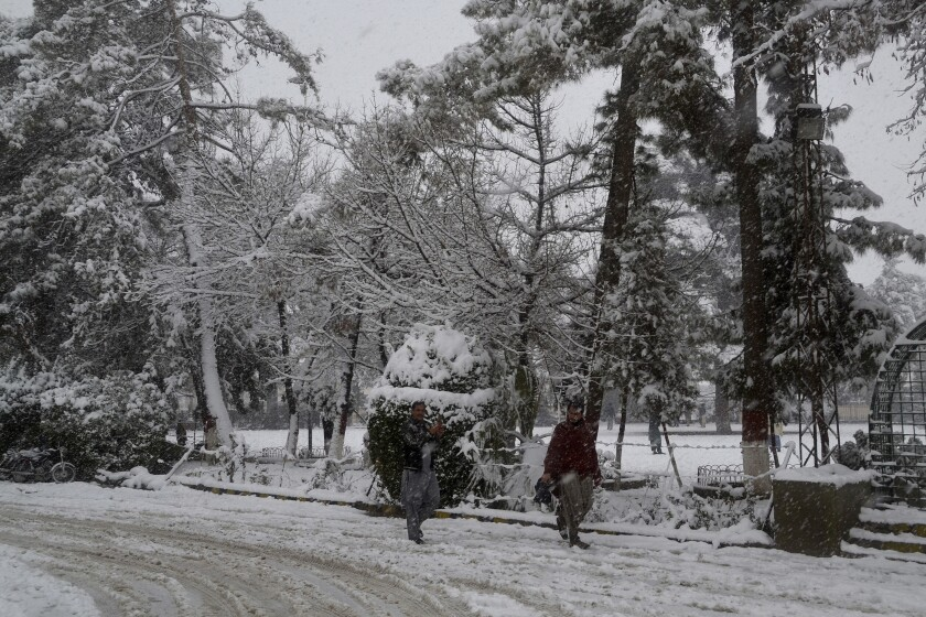 People walk along a road during heavy snowfall in Quetta, Pakistan, on Sunday.