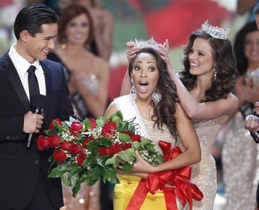 Host Mario Lopez watches Miss Virginia Caressa Cameron react after being crowned Miss America by Miss America 2009 Katie Stam, Saturday Jan. 30, 2010 in Las Vegas. (AP Photo/Eric Jamison)