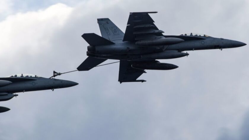 An F/A-18F Super Hornet refuels an EA-18G Growler