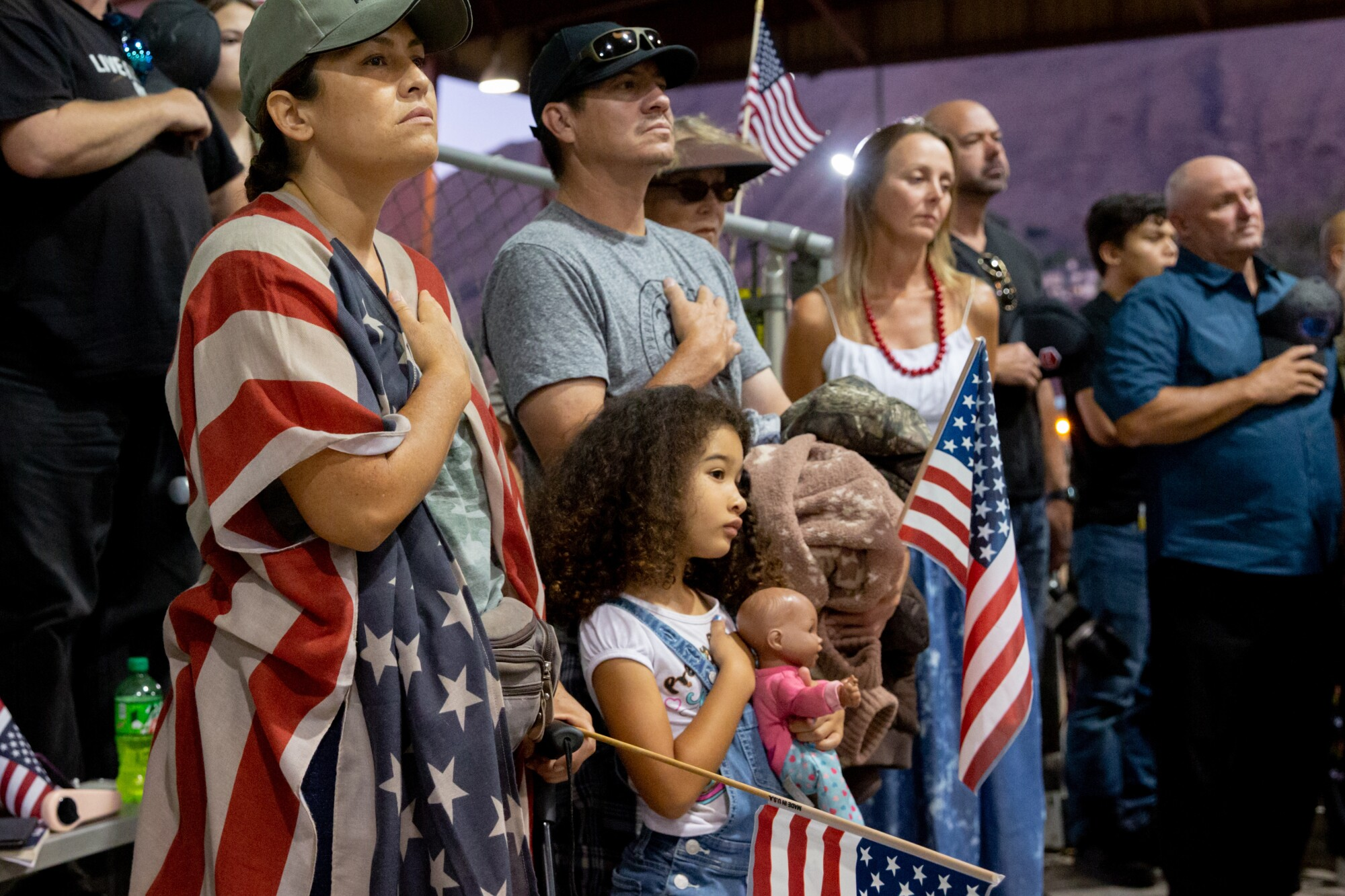 Malina Shaw says the pledge of allegiance with her family during a vigil