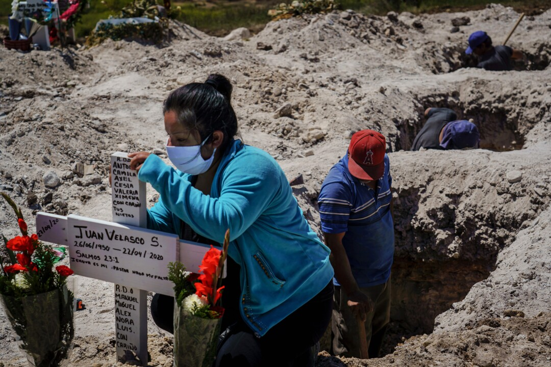 At Tijuana's Municipal Cemetery No. 13, Nora Lassete marks the burial cross after the funeral of Juan Velasco, who died of COVID-19 symptoms.