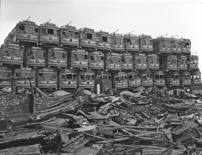 Old Pacific Electric red cars sit at a Terminal Island junkyard in 1956, awaiting dismantling to become scrap metal.