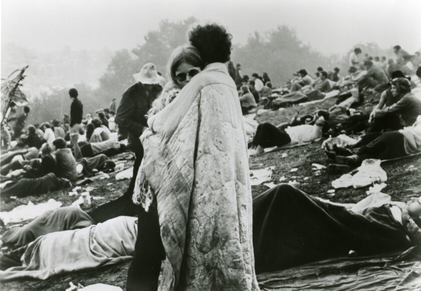 A couple huddles as others rest and relax at Woodstock. The legendary 1969 music festival in upstate New York irrevocably changed youth culture and the concert industry.