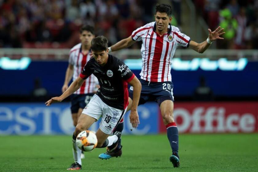 Jesús Molina (d), de Chivas, disputa la bola con Mauro Lainez (i), de Lobos BUAP durante un juego celebrado en el estadio Akron de Guadalajara (México). EFE/ Francisco Guasco/Archivo
