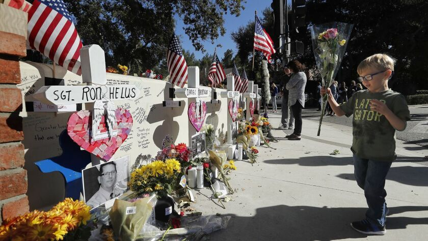 Ben Alexander, 4, of Westlake Village places flowers next to each cross at a makeshift memorial for victims of the Borderline Bar and Grill shooting outside the bar.