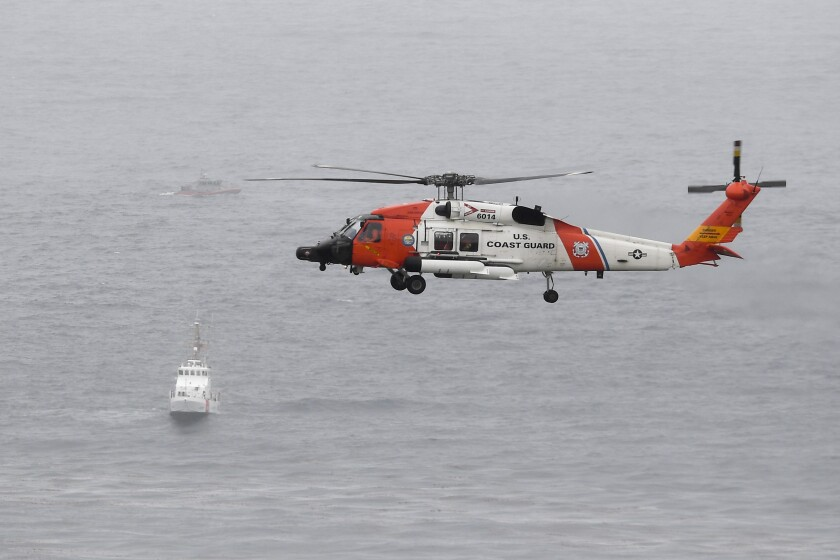 A U.S. Coast Guard helicopter flies over boats searching the area where a boat capsized