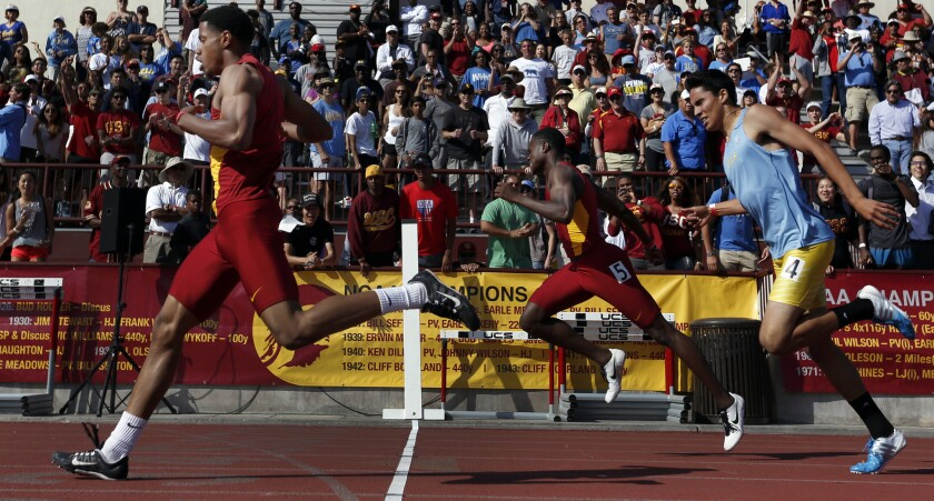 USC senior Davonte Stewart, left, crosses the finish line first during the men's 400 meter dash in the USC-UCLA track meet.