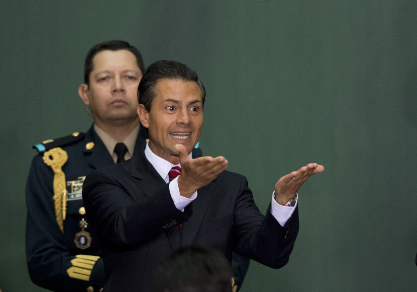 Mexican President Enrique Peña Nieto gestures during the signing ceremony for a historic energy reform bill at the National Palace in Mexico City on Monday.
