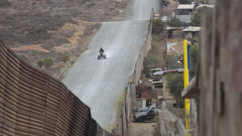 A Border Patrol agent riding on an ATV heads west on the access road adjacent to the border barrier in the Nido de las Aguilas section of Tijuana.