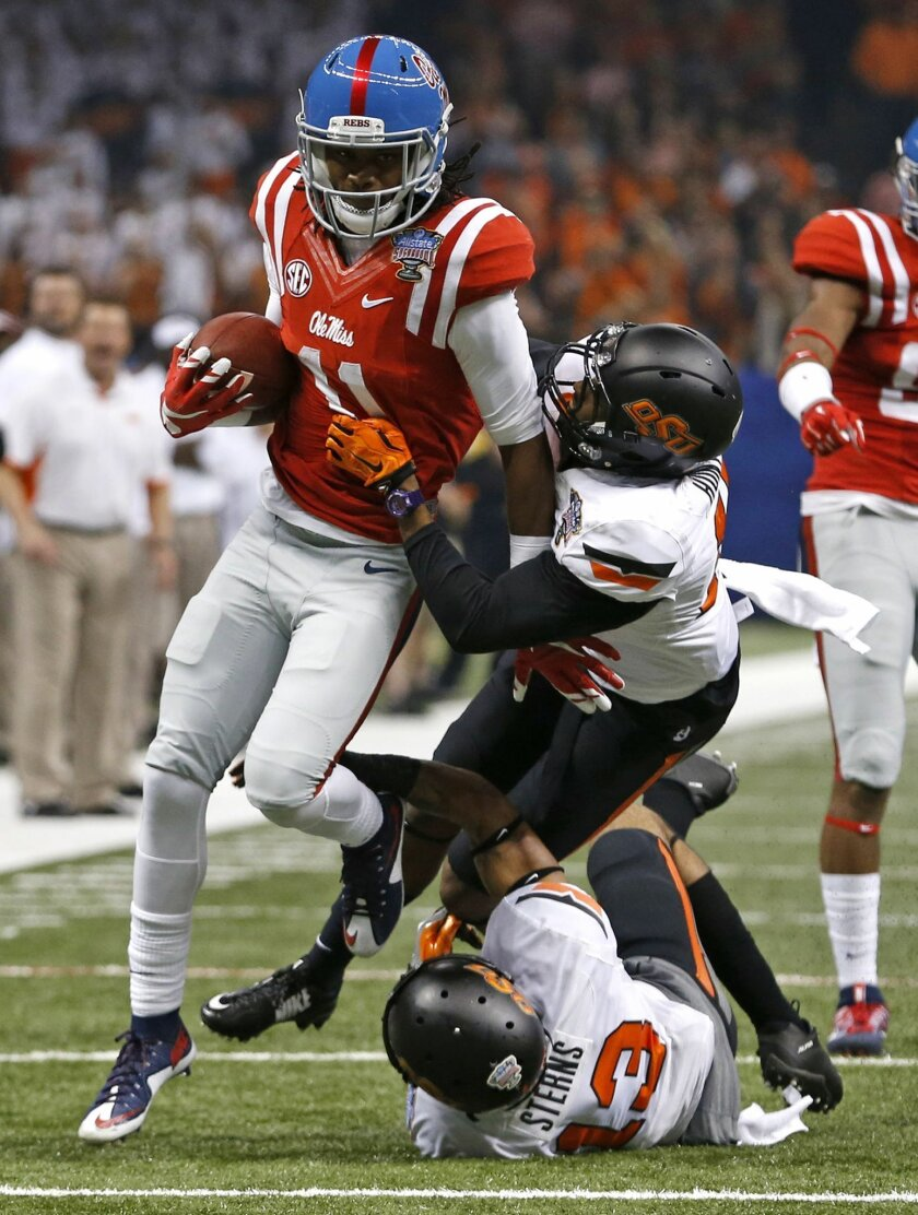 Mississippi wide receiver Markell Pack (11) carries as Oklahoma State safety Jordan Sterns (13) and cornerback Michael Hunter (17) try to tackle in the first half of the Sugar Bowl college football game in New Orleans, Friday, Jan. 1, 2016. (AP Photo/Jonathan Bachman)