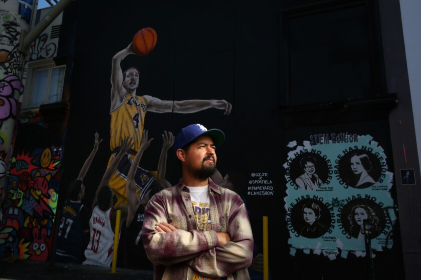 Artist Gustavo Zermeño Jr. stands in front of a mural he painted of Lakers guard Alex Caruso on Nov. 22.