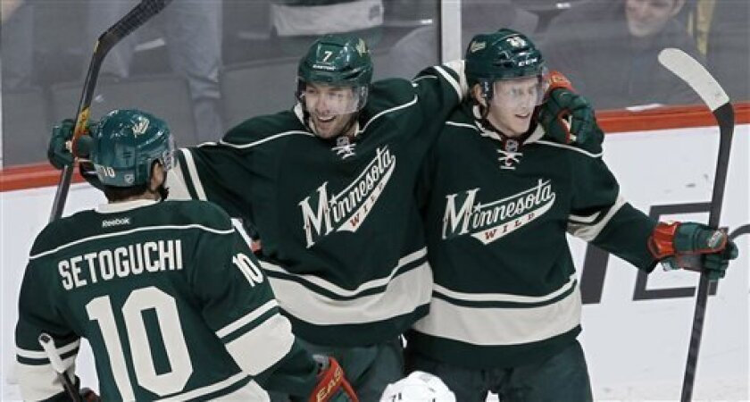 Minnesota Wild center Matt Cullen, center, celebrates with teammates Jonas Brodin, right, and Devin Setoguchi (10) after Cullen scored during the first period of an NHL hockey game against the Los Angeles Kings in St. Paul, Minn., Saturday, March 30, 2013. (AP Photo/Ann Heisenfelt)
