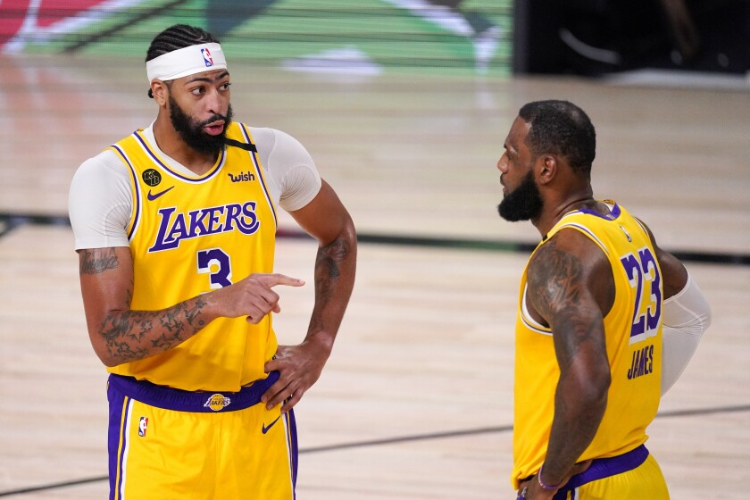 Lakers stars Anthony Davis (3) and LeBron James talk strategy during a break in a playoff game against the Nuggets.