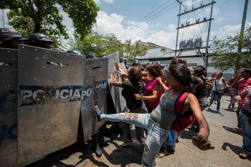 Un grupo de familiares de presos protesta ante miembros de la Policía en las inmediaciones del centro de reclusión de la Policía Estatal de Carabobo (centro) en Valencia (Venezuela). EFE/Archivo