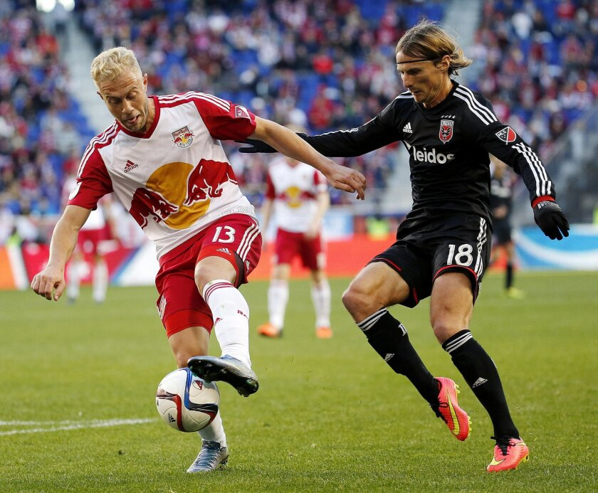 New York Red Bulls forward Mike Grella, left, dribbles against D.C. United forward Chris Rolfe during the first half of an MLS playoff soccer match, Sunday, Nov. 8, 2015, in Harrison, N.J. (AP Photo/Julio Cortez)