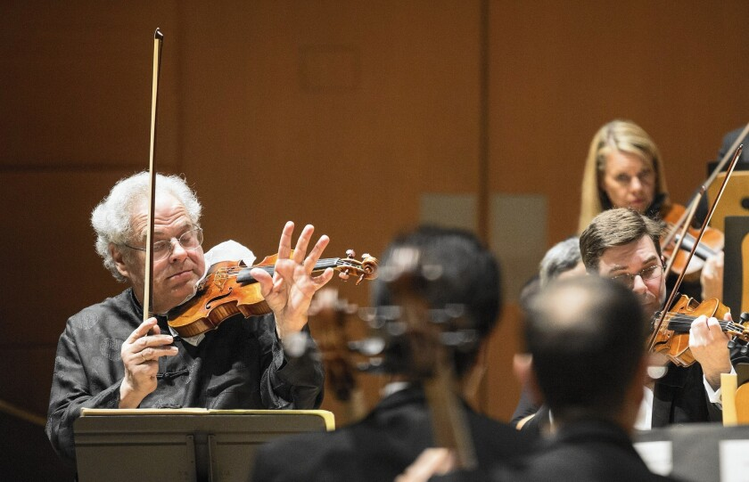 Itzhak Perlman plays violin while simultaneously conducting the L.A. Philharmonic on Thursday at Walt Disney Concert Hall.