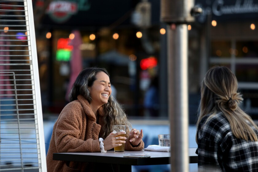 People sit unmasked at an outdoor table in Redondo Beach.