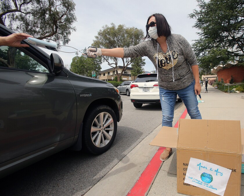Caroline Anderson uses barbecue tongs to pass out a packet of 10 face masks to a person in their car as part of the Chinese Club of La Cañada Flintridge and La Crescenta's Masks for Many program to help senior citizens in the community protect themselves amid the coronavirus outbreak.