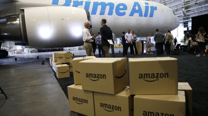 FILE - In this Aug. 4, 2016 file photo, Amazon.com boxes are shown stacked near a Boeing 767 Amazon