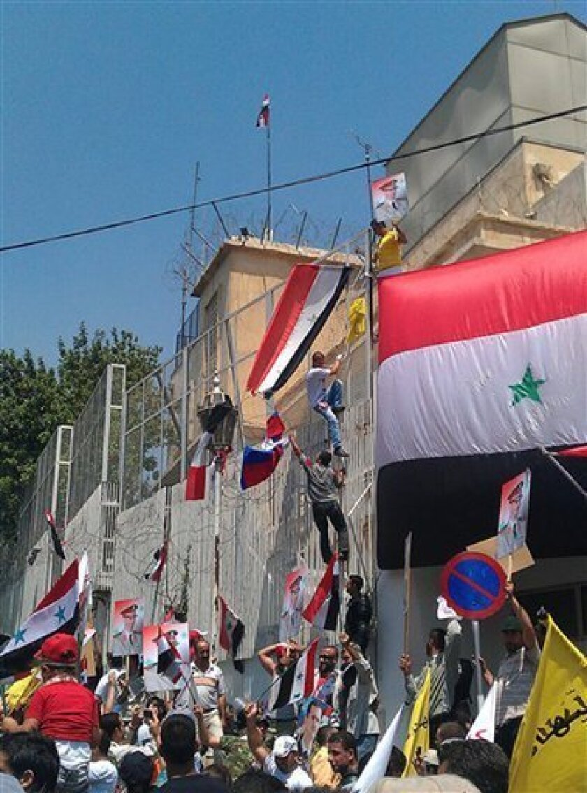 In this photo released by a Syrian news website Shukumaku and according to them, pro-Syrian President Bashar Assad protesters, hang Syrian flags and Assad portraits at the fence wall of the US the embassy compound as they protest against the US Ambassador Robert Ford after his visit on Friday to the Syrian city of Hama, in Damascus, Syria, Monday, July 11, 2011. A U.S. official says the Obama administration will formally protest an attack on the American Embassy in Syria and may seek compensation for damage caused when a mob breached the wall of the compound before being dispersed by Marine guards.(AP Photo/Shukumaku Syrian News Website) EDITORIAL USE ONLY