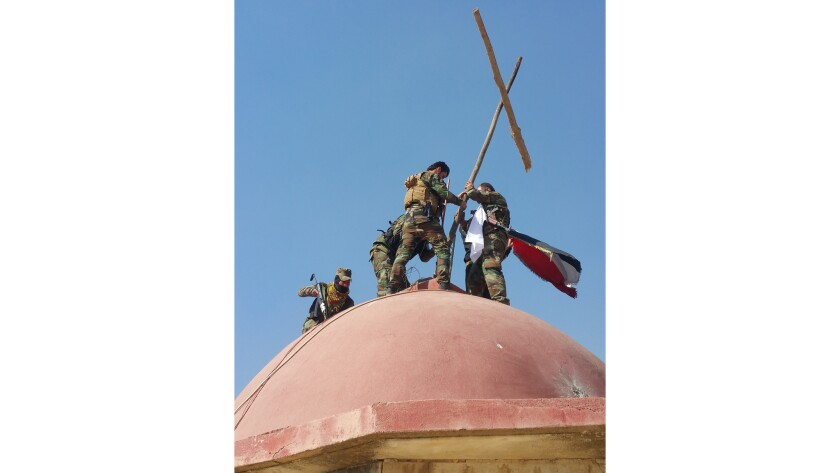 Members of a Christian militia hoist a make-shift cross atop the Mar Shmony Church in Bartella. Islamic State fighters, who espouse a harsh interpretation of Sharia or Islamic law, tore down all crosses when they overran the town two years ago.