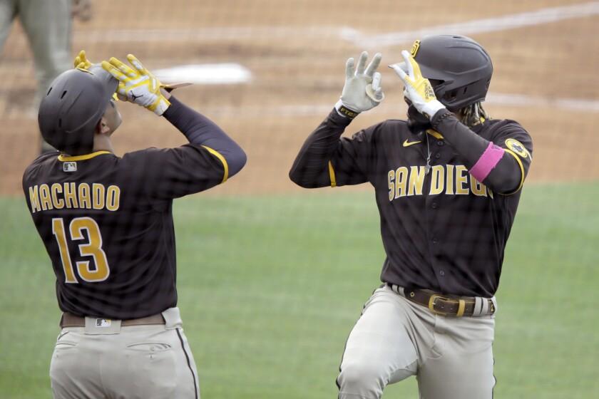 Los jugadores de los Padres de San Diego Fernando Tatis Jr., a la derecha, celebra su jonrón solitario